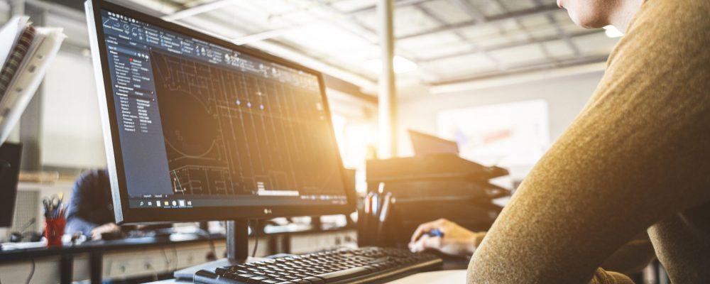 Engineer designer working on desktop computer in factory.